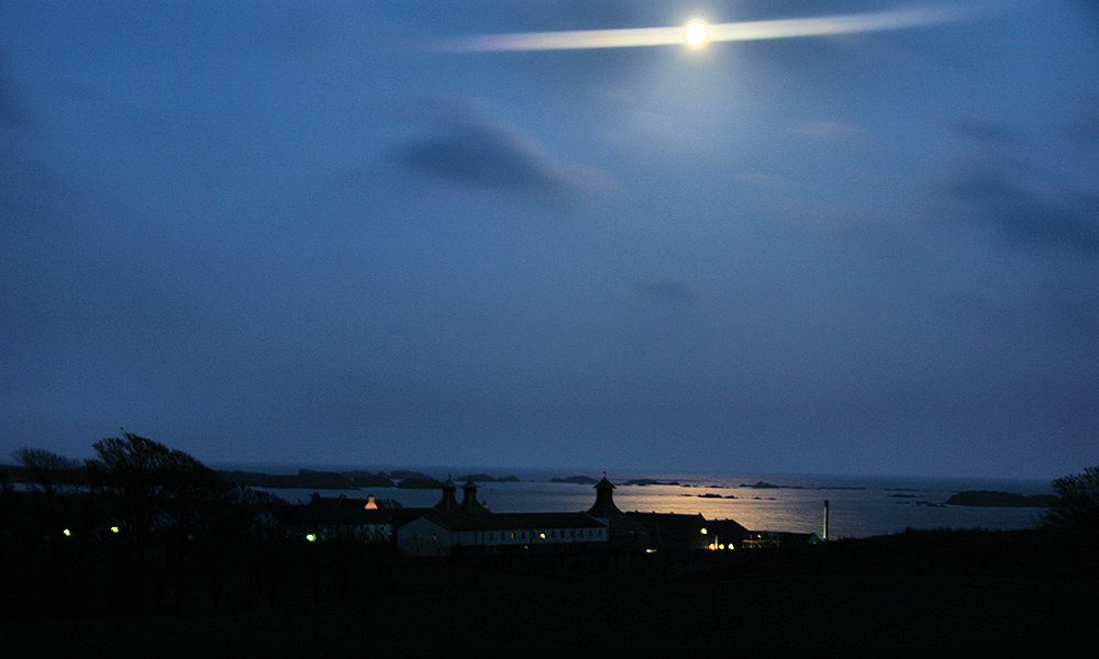 Picture of the Moon above a coastal distillery, the Moon reflecting in the water