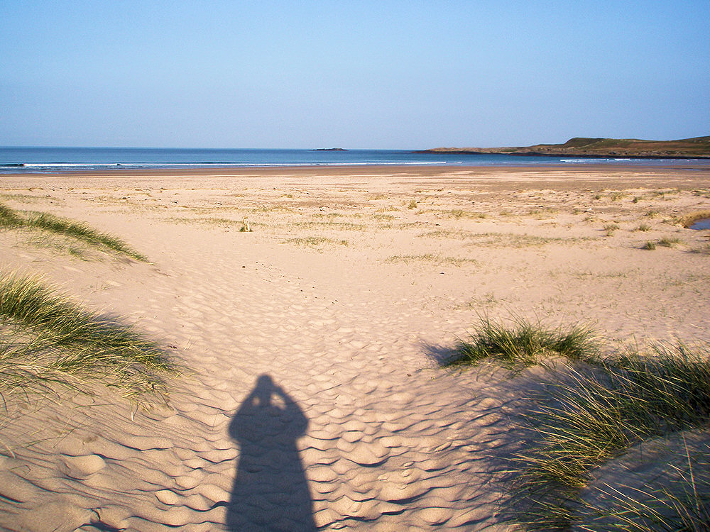 Picture of a beach coming through some dunes, a long shadow of the photographer ahead