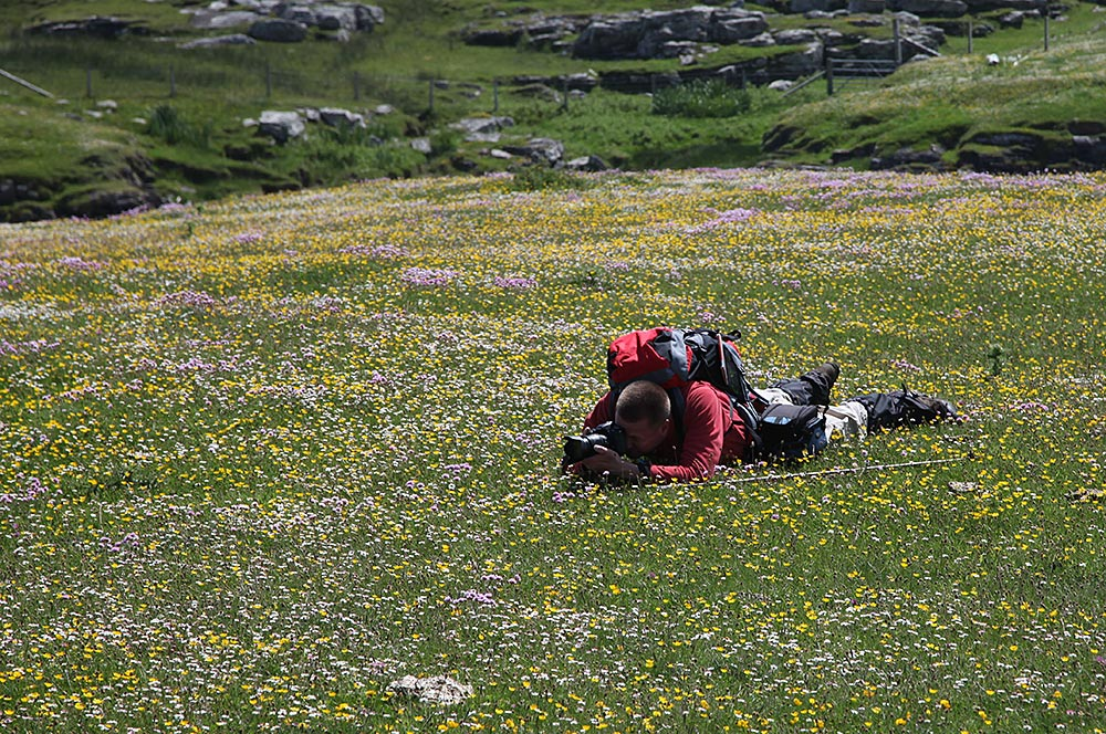 Picture of a man lying on the ground photographing a machair landscape
