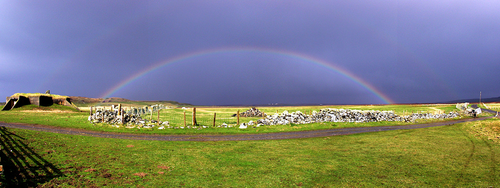 Panoramic picture of a full rainbow above farmland