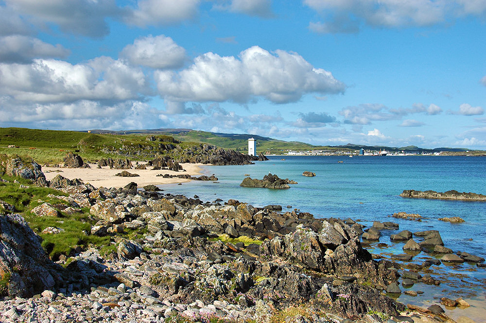 Picture of a small beach next to a lighthouse, a coastal village in the distance