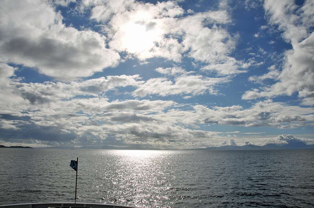 Picture of a view ahead from a ferry, bright sunshine and clouds in the sky