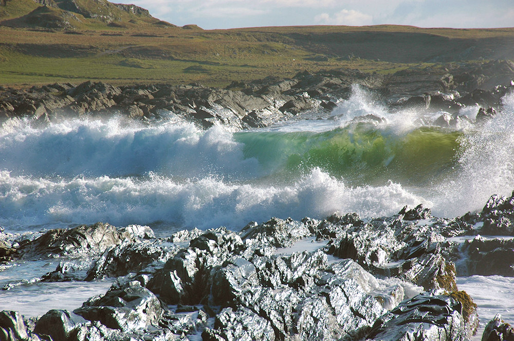 Picture of waves breaking in a bay with a mixture of beach and rocks