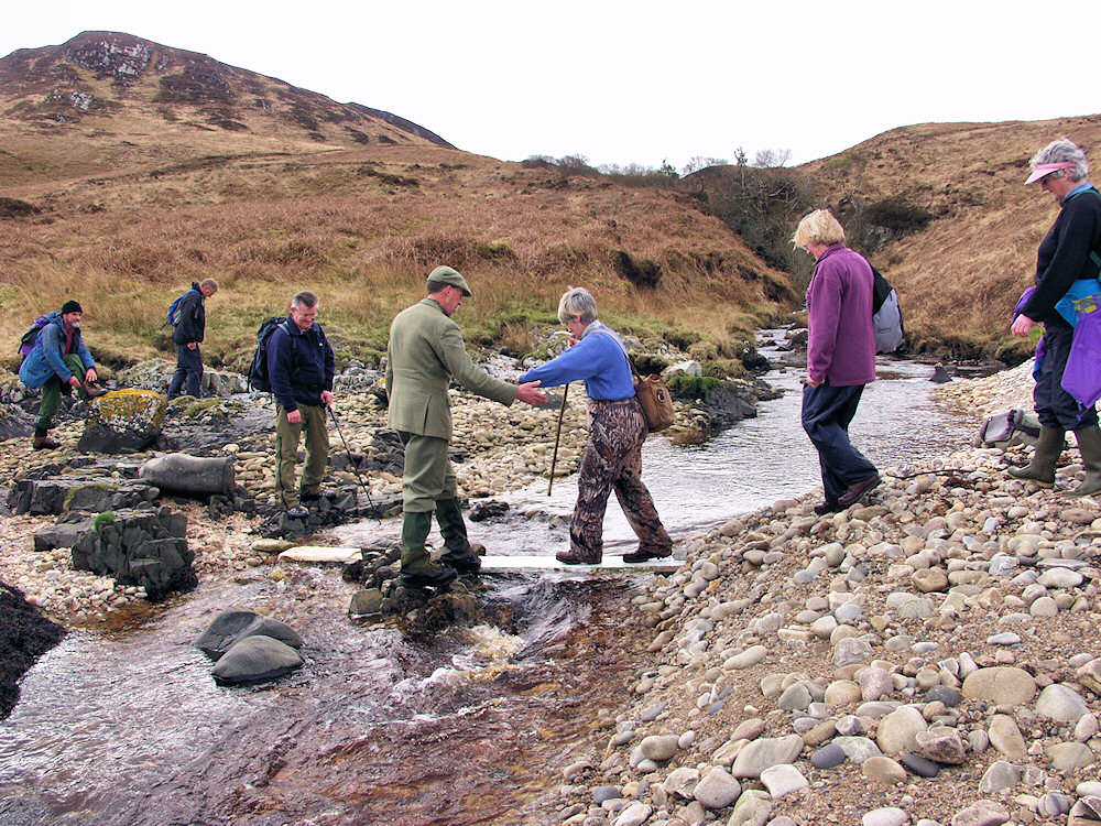 Picture of a group of walkers crossing a burn
