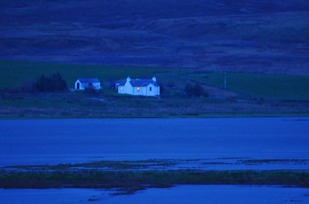 Picture of a cottage in the evening seen across a sea loch