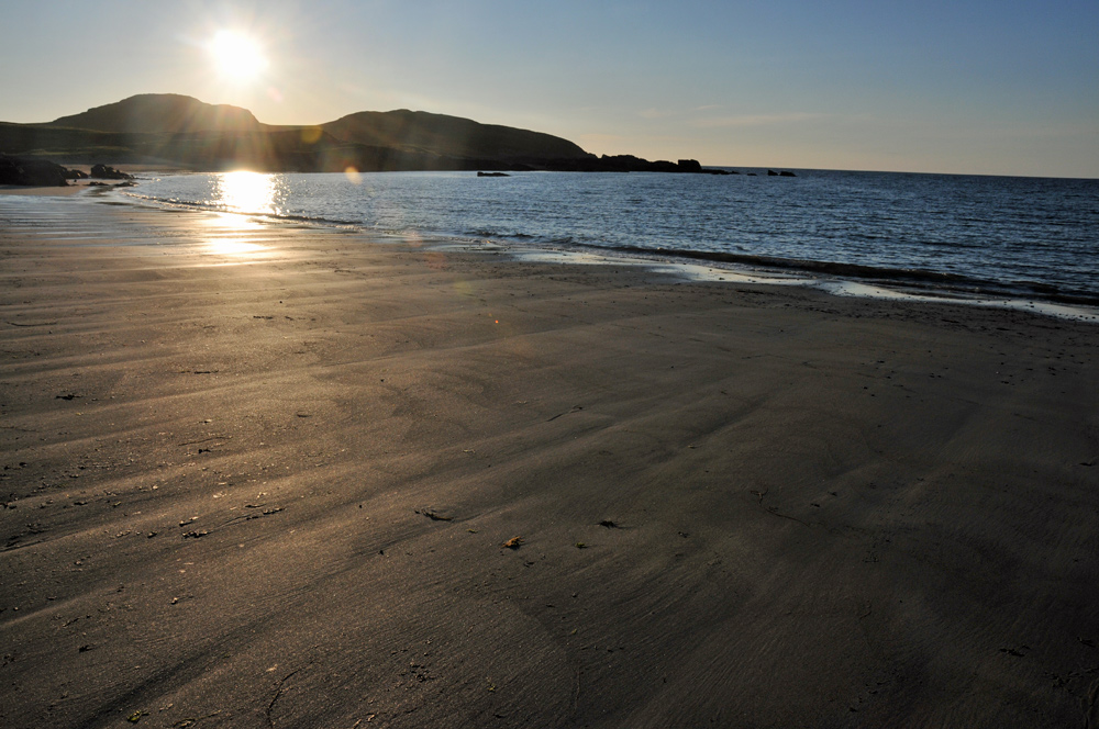 Picture of the low evening sun over a bay with a beach