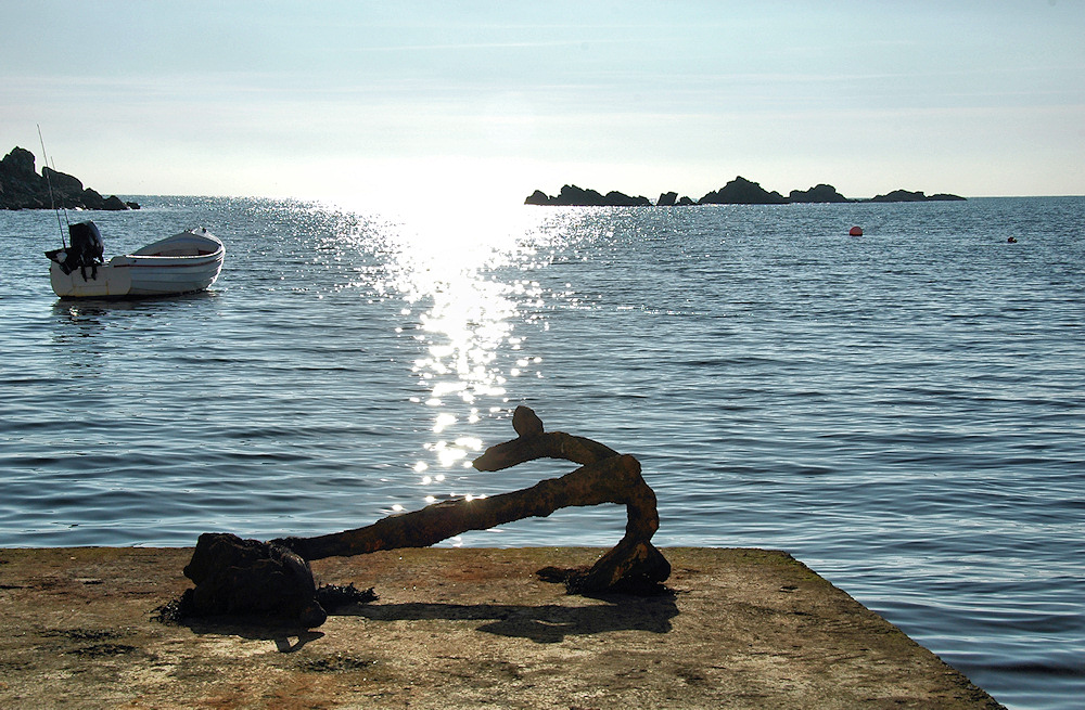 Picture of a rusty old anchor on a small pier at a sea loch in bright sunshine