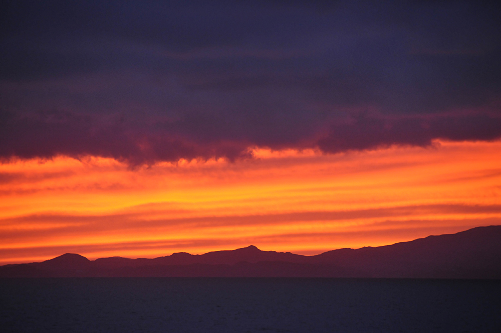 Picture of a very colourful sunset over an island seen from a ferry