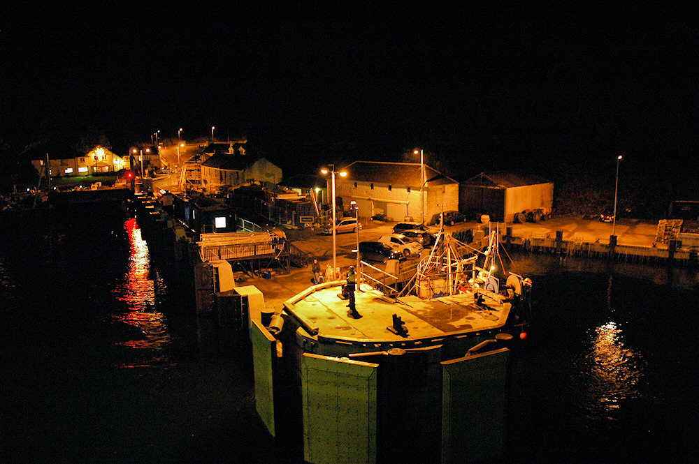Picture of a ferry port at night, seen from an arriving ferry