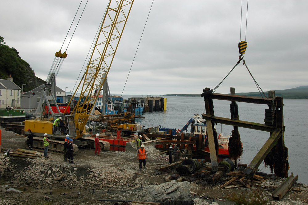 Picture of a crane lifting out an old harbour pier structure