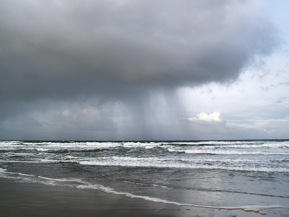 Picture of a rain front moving into a bay with a beach