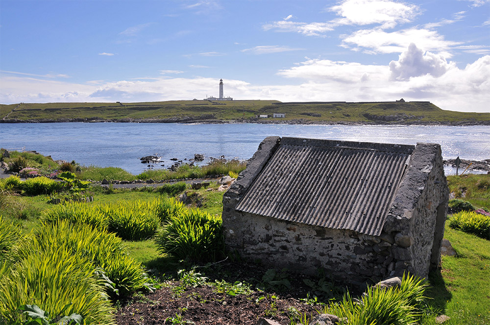 Picture of a view over a shed at a coastal path, a lighthouse on an offshore island