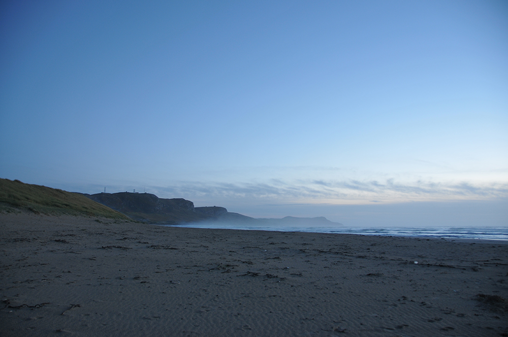 Picture of a bay with a beach just after sunset, mist rolling in from the sea
