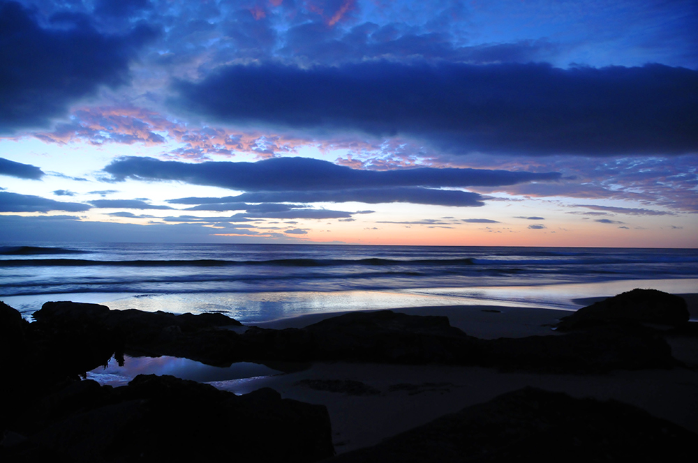 Picture of a view out to sea from a beach during the gloaming