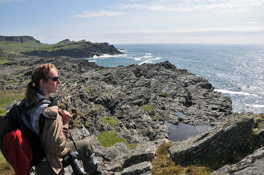 Picture of a woman enjoying a view over a coast with rugged cliffs
