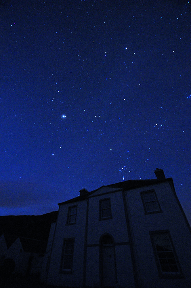 Picture of a large house at night, a sky with many stars above
