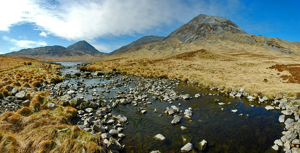 Picture of a small river with stepping stones, three big mountains (The Paps of Jura) behind it
