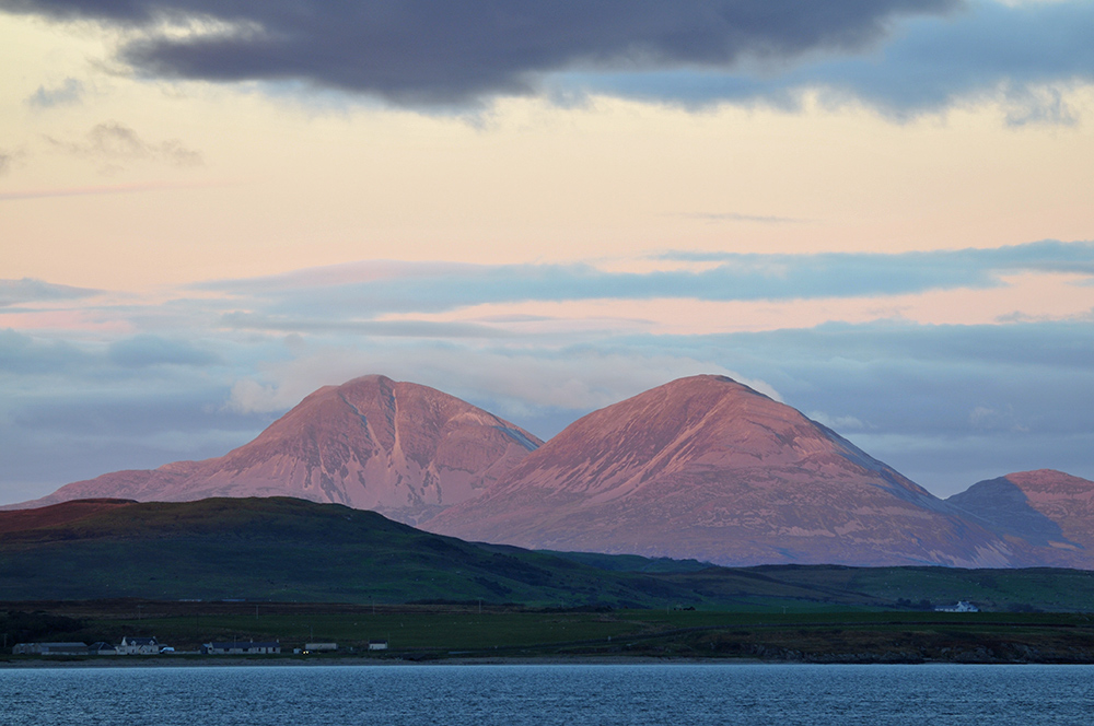 Picture of two mountains in the red evening light, seen behind low hills across a sea loch
