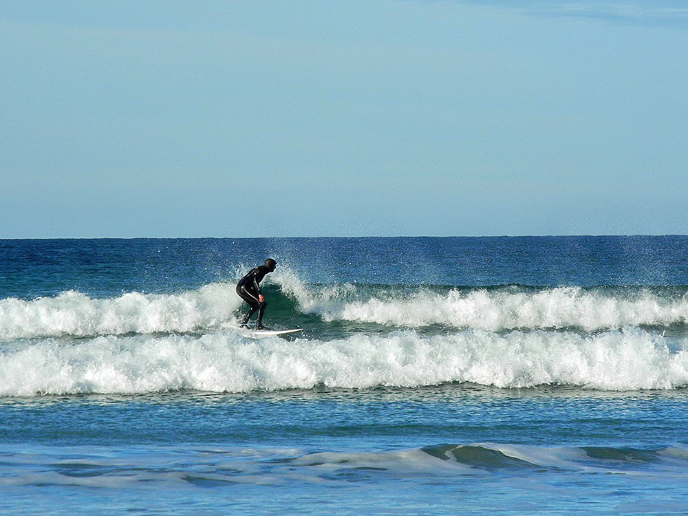 Picture of a surfer riding a wave on a sunny October day