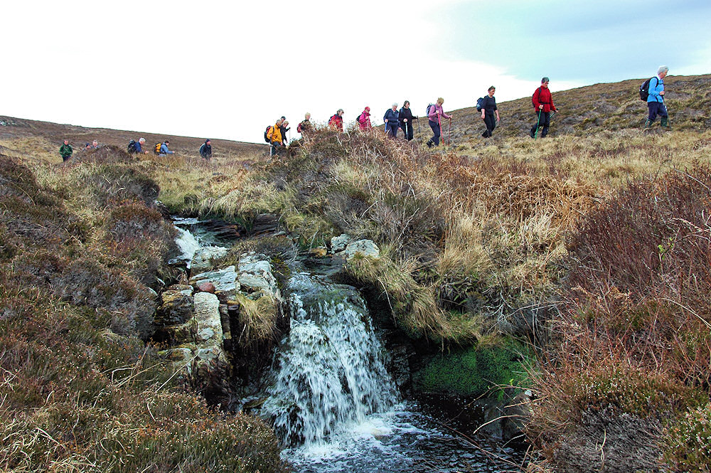 Picture of a group of walkers passing a small waterfall