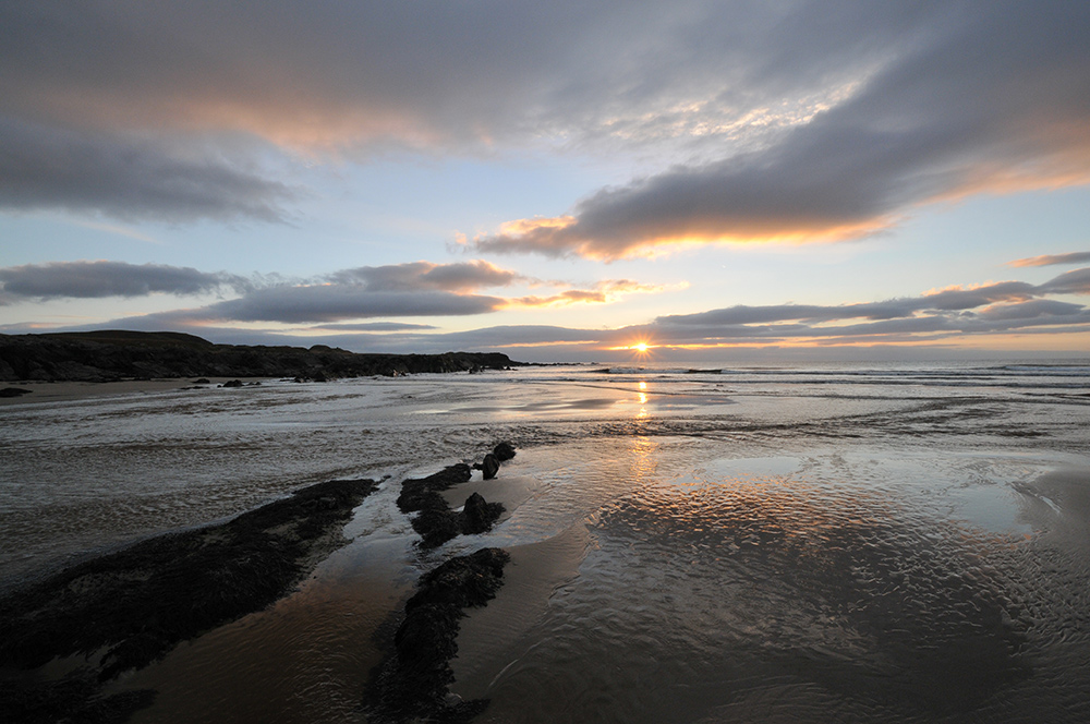 Picture of a wide angle lens view of a sunset at a bay with a beach