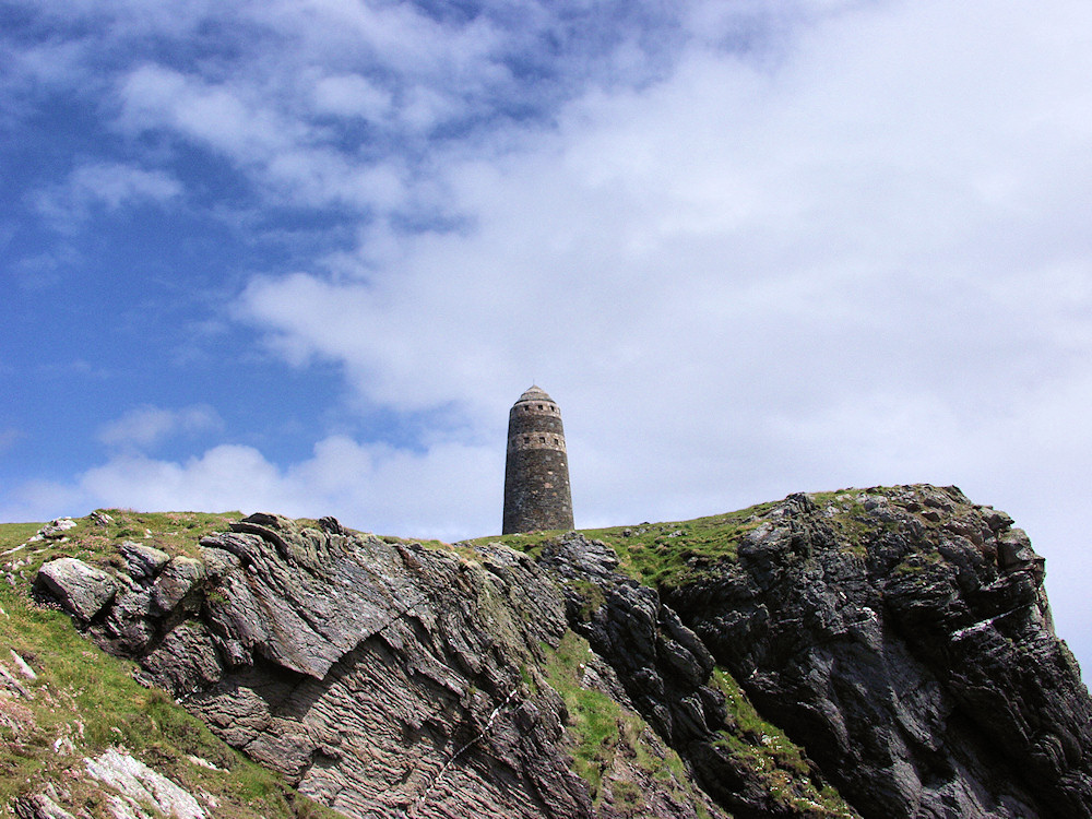 Picture of a view up some cliffs with a monument (the American Monument on the Oa, Islay) on top