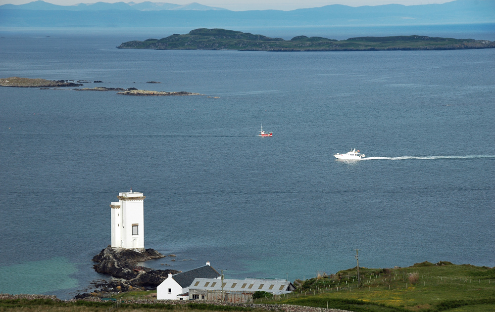 Picture of a lighthouse at the entrance to a bay, two boats passing in opposing directions