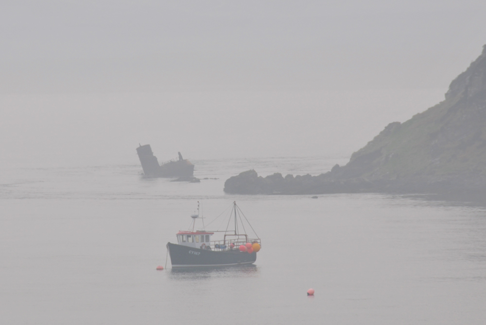 Picture of a fishing boat and a wreck in the mist