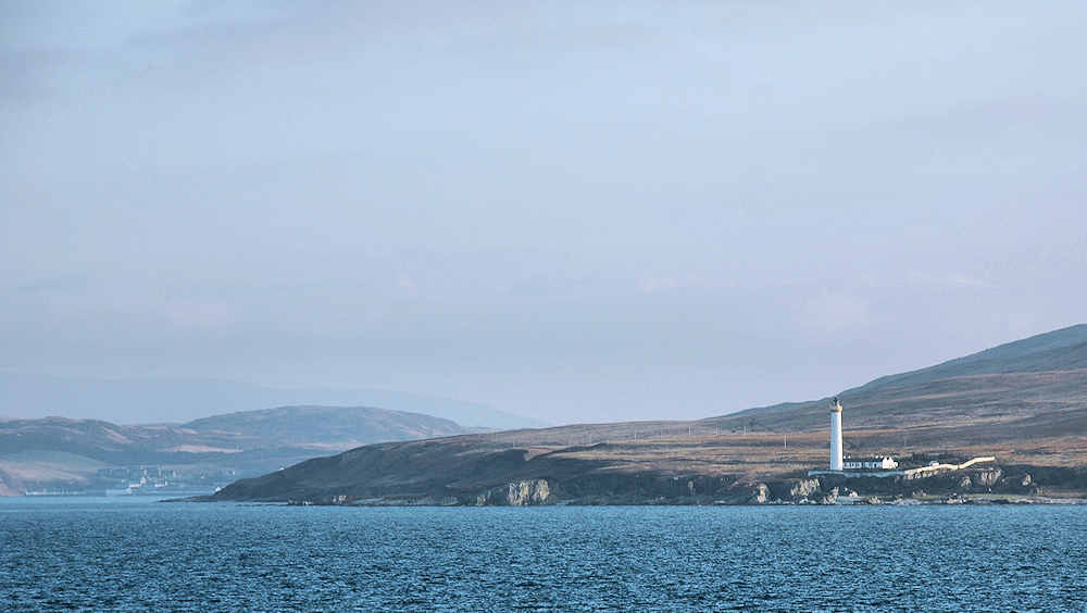 Picture of a view from a ferry to an Islay, a lighthouse on the right, a village with a distillery on the left
