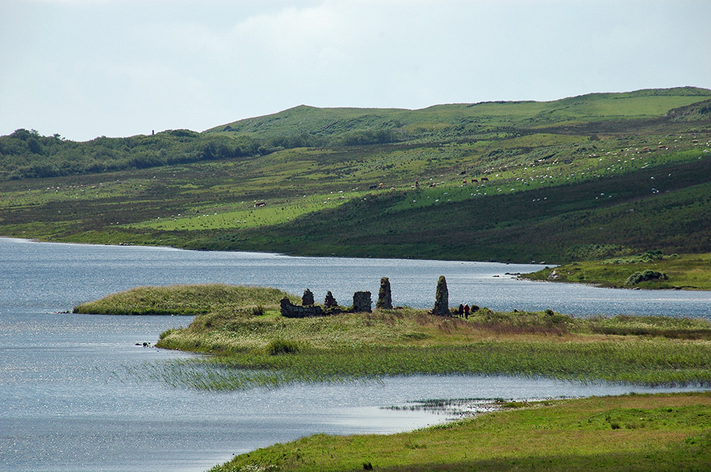Picture of a view over a loch with two small islands, one with the ruin of houses