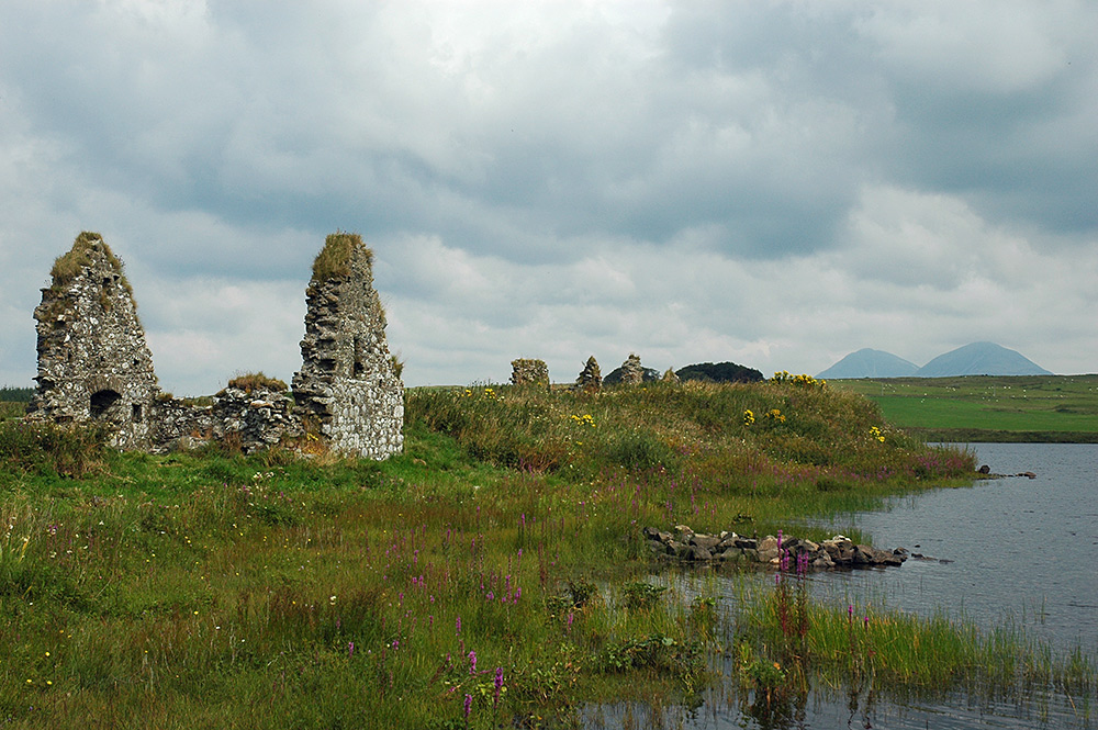 Picture of ruined buildings on a small island in a loch, large mountains in the background