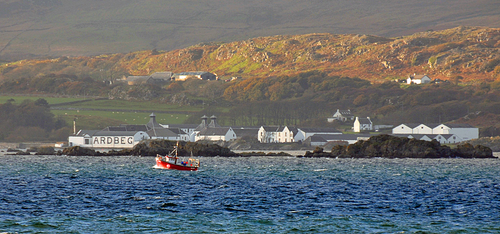 Picture of a small red fishing boat passing the Ardbeg distillery on Islay in the afternoon light