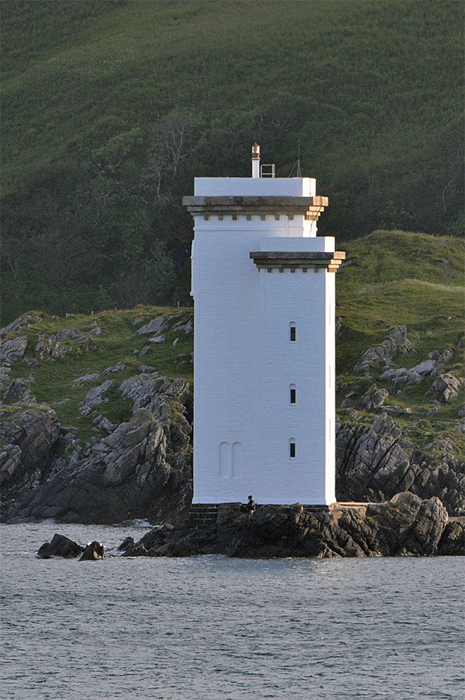 Picture of a square lighthouse with a man fishing standing at the foot