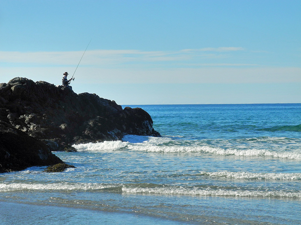 Picture of man fishing from some rocks at the end of a sandy beach