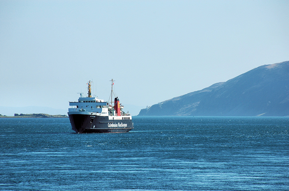 Picture of a ferry in a sound between two islands, a lighthouse also visible in the distance