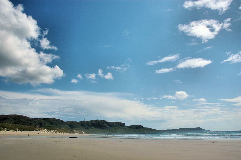 Picture of a wide sandy beach in sunshine, some clouds in the sky