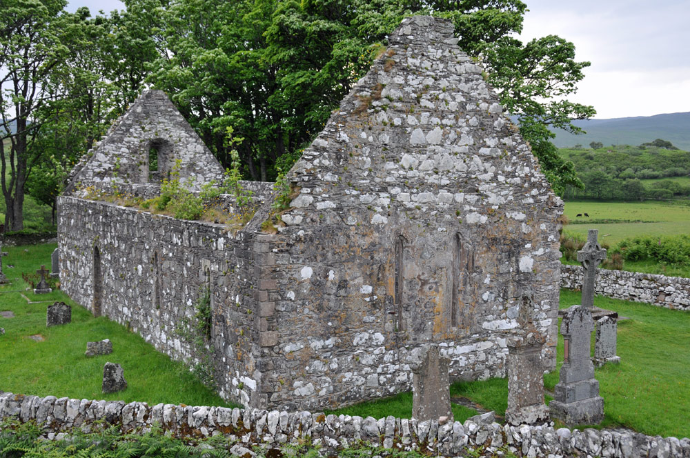 Picture of a ruined church, a Celtic cross next to it