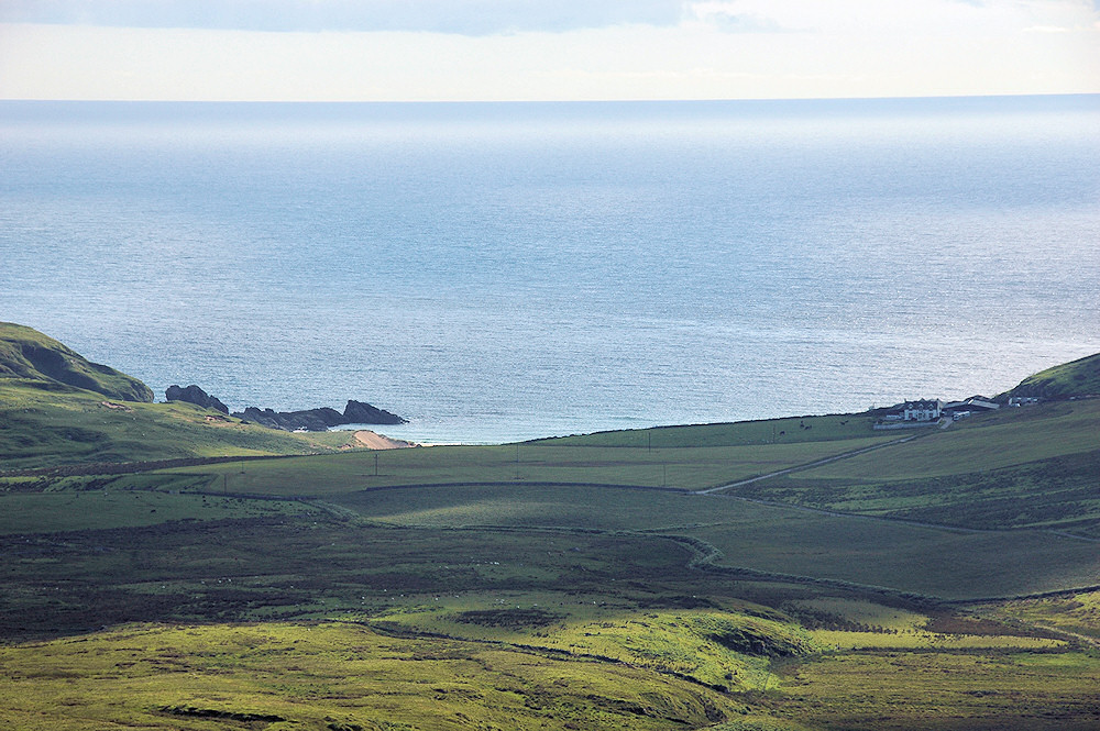 Picture of a view from a hill over a coastal landscape with a bay and a farm