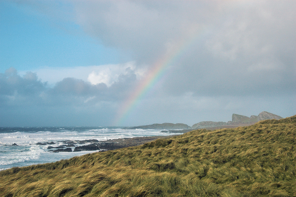 Picture of a (faint) rainbow at a bay with waves rolling in, view from the dunes