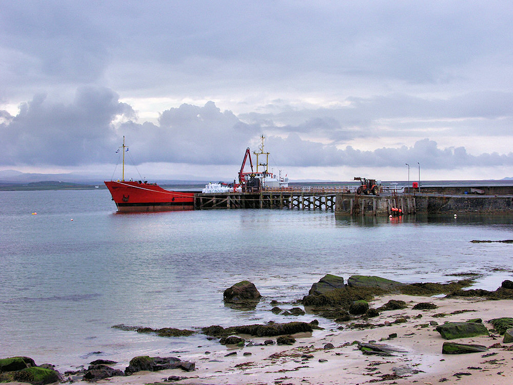 Picture of a small cargo ship unloading at a pier