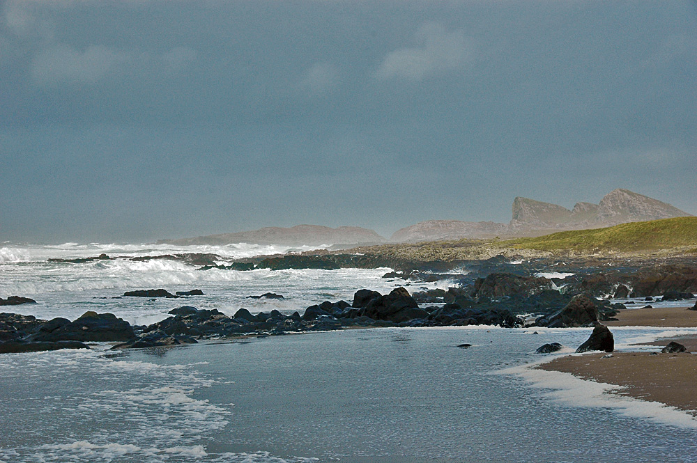 Picture of a bay with white waves rolling in under a dark sky