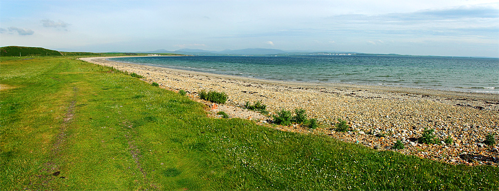 Panoramic picture of a long stretch of pebble beach