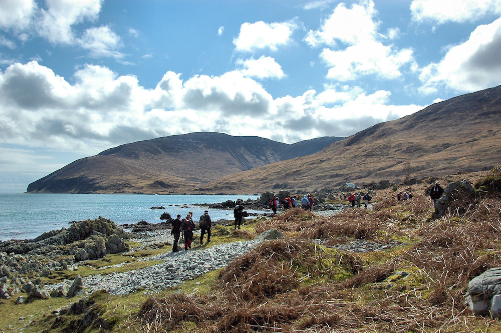 Picture of a group of walkers approaching a bothy on the shore of a sound between two islands