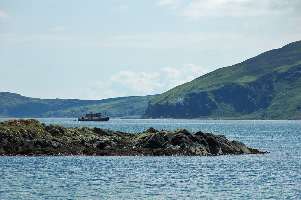 Picture of a small cruise ship entering a sound, a lighthouse visible on the other side of the sound