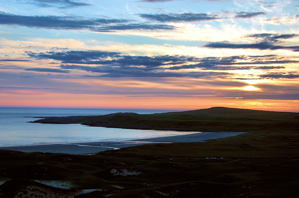 Picture of a view over a bay with sunset approaching, colourful clouds in the sky