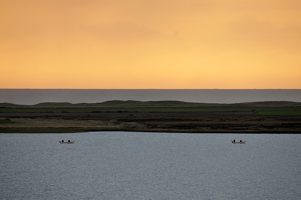 Picture of two small boats with people fishing on a loch, colourful sky above