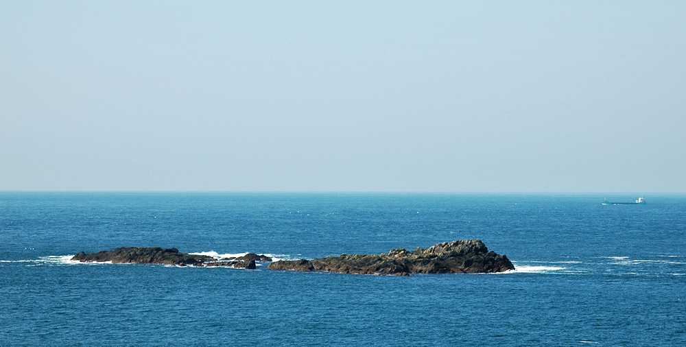 Picture of some treacherous rocks and a ship passing in respectful distance