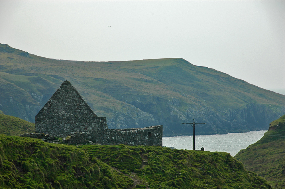 Picture of the ruins of a chapel, a bay in the background