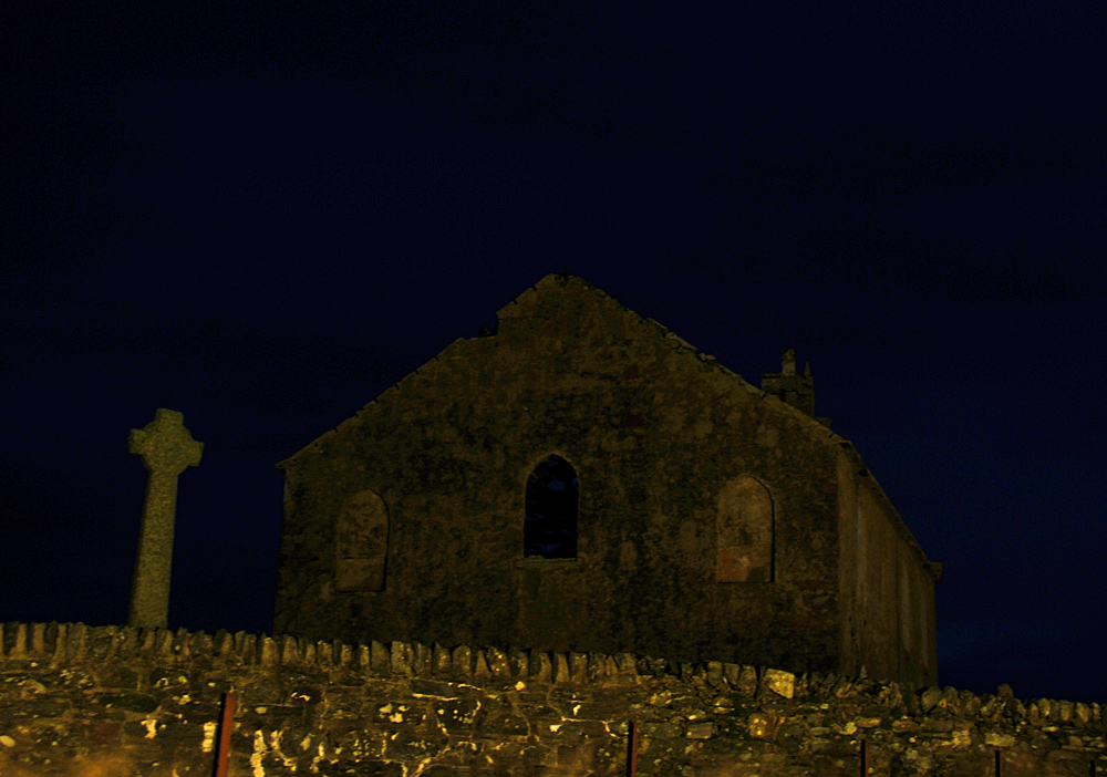 Picture of a Celtic cross and a ruined church at night