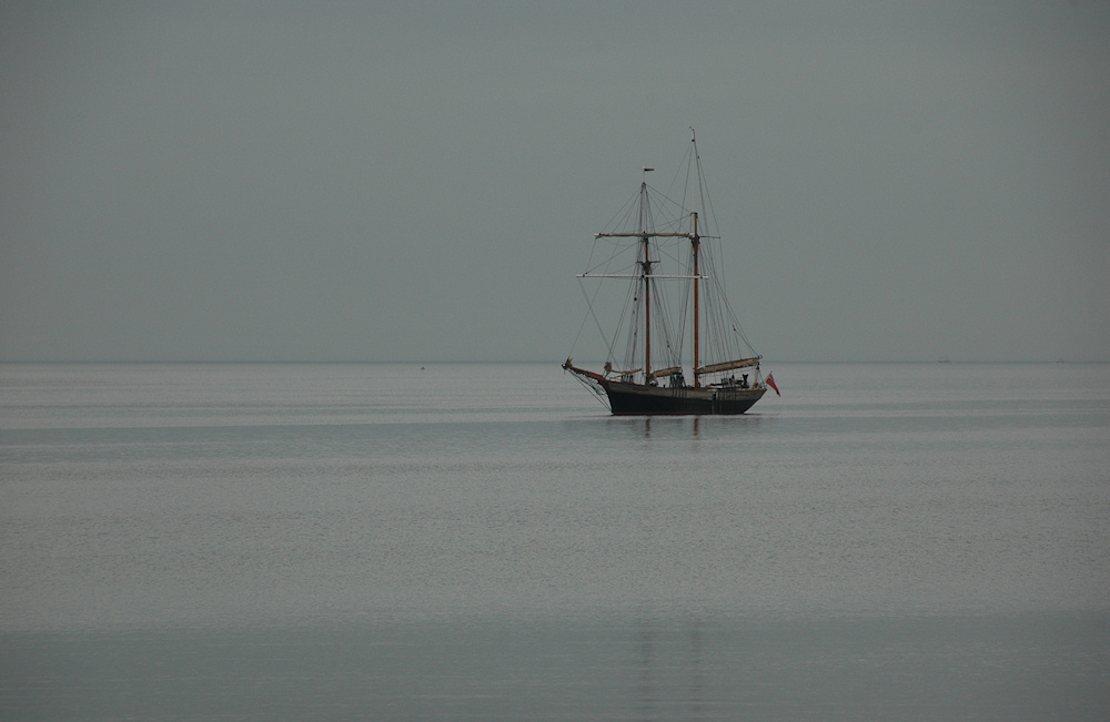 Picture of a sailing ship anchored in a bay on a grey day